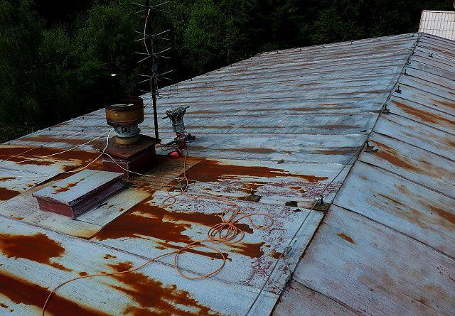 Čištění zanedbané střechy v Rudě před nátěrem, očištěná vsneočištěná část