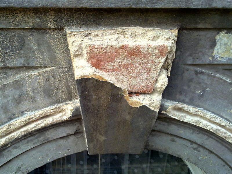Detail poškozené ozdobné profilace nad oknem