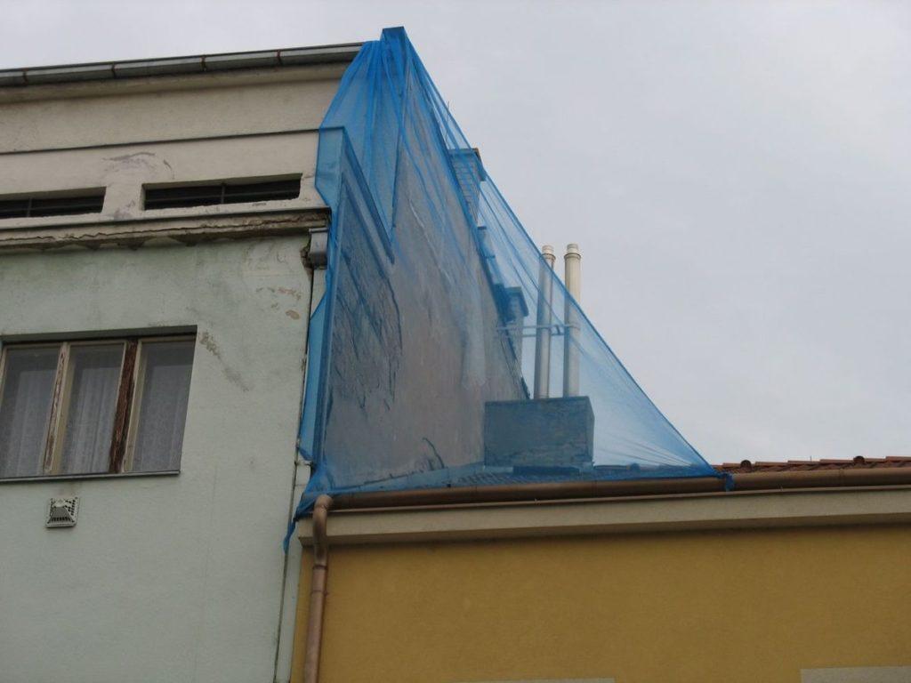 Oprava bočního štítu zajištěná sítí proti pádu omítky na chodník